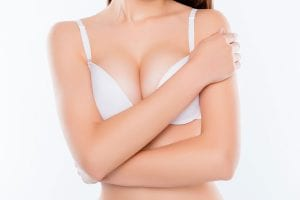 Woman covering her self in a white bra.