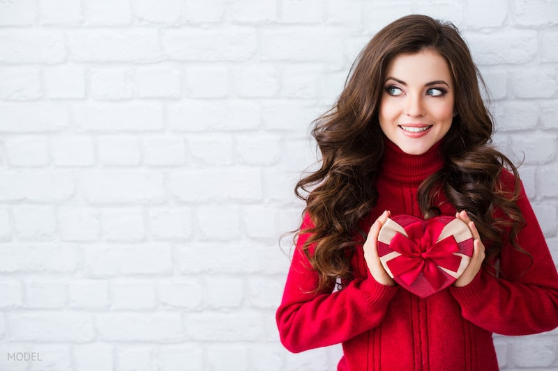 Woman wearing a red sweater holding a wrapped heart for Valentine's Day